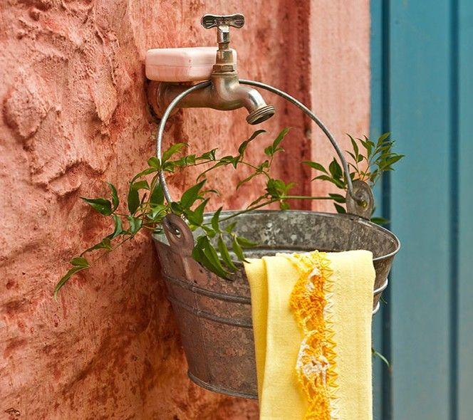 Pia improvisada! Faça um furo embaixo do balde para o escoamento da água e pendure-o numa torneira externa. Só não se esqueça da toalha de mão