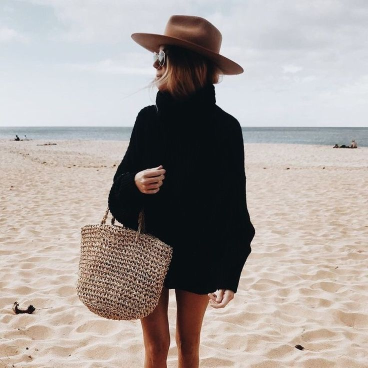 Oversized black sweater with cute brown hat and straw bag.