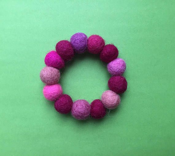 This felt bracelet is made from hand-rolled Merino wool beads in a variety of pink shades. Its stretchy and a lightweight, eye-catching piece.  ~ handmade wool beads ~ stretch material ~ made from 13 1.5cm felt balls ~ the final photo shows this item alongside my other felt bead bracelets  See more of my bracelets here - https://www.etsy.com/shop/NineAngels?section_id=20455250