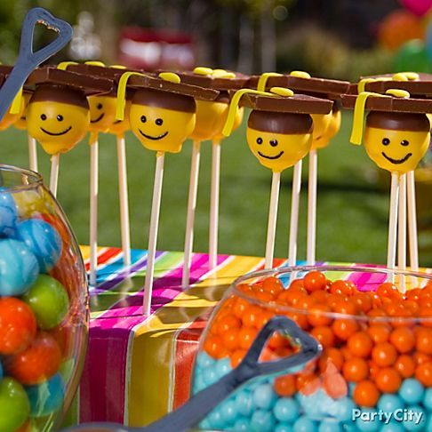 Dip cake pops in white chocolate candy melt tinted yellow using gel icing color. Add a square of candy bar to the top to look like a grad cap. Dip the top in chocolate candy melt, then use a black icing tube to draw a simple smiling face on your pops.