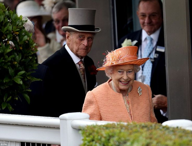 High spirits: The Queen, who wore a paisley-patterned dress beneath her coat, smiled as she and Prince Philip entered the Royal Enclosure