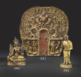 STATUETTE DE KASHYAPA EN BRONZE DORE TIBETO-CHINOIS, FIN DU XVIIIEME SIECLE Représenté debout sur une base lotiforme séparée et plus ancienne, les deux mains tenant un attribut à l'origine, vêtu de la robe monastique rehaussée d'un galon de fleurs incisées, le visage ridé, le crâne rasé, rescellé Hauteur avec la base: 20,5 cm. (8 in.)