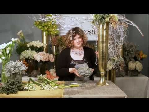 The Art of Flowers January 2012 - The Art of Flowers video debut, Mandy creates 2 large entrance pieces that would be perfect for New Year's celebrations and parties. She creates stunning pieces using the Mayesh Certified Awesome Blossom, Dusty Miller, along with lace leaf dusty miller, flocked branches, agapanthus, white hydrangea, white anemones, and oscularia succulents.