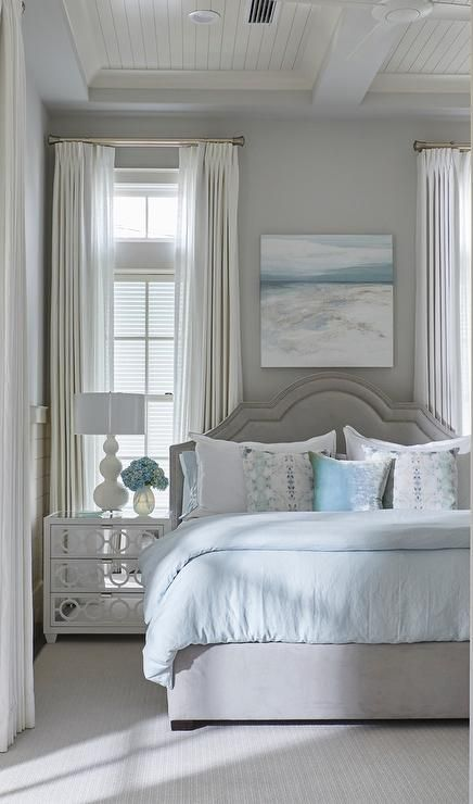 Blue and gray beach style bedroom features a gray velvet bed with curved gray headboard dressed in white and pale blue bedding placed next to a white mirrored 3-drawer nightstand, Worlds Away Ava White Lacquer Nightstand, and a white triple gourd lamp placed under a window dressed in white drapery panels.