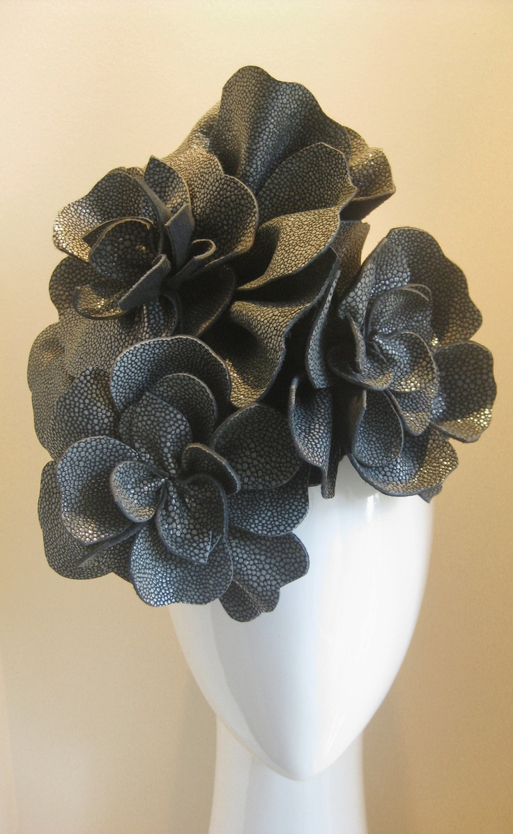 Industrial flowers. Made from the most amazing textured leather that is hard to see from the photos, but is almost like the beadwork look from the planet dress. One supersized flower and two smaller are handcut, hand stitched and balanced onto a handmade black felt base with comb and elastic for easy all day wearing. A great winter neutral.