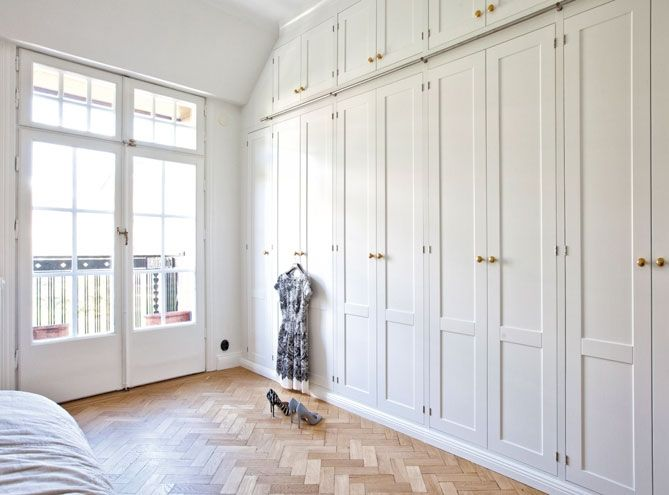 Charming Wall Of White Closets With Storage Closets Above For A Small Bedroom.