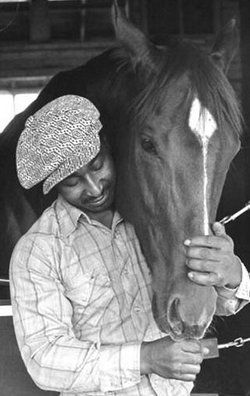 Eddie and his baby share a moment. The softness of Secretariat's eye and Eddie's smile, that blossoms from somewhere deep, deep inside, depict a timeless connection.