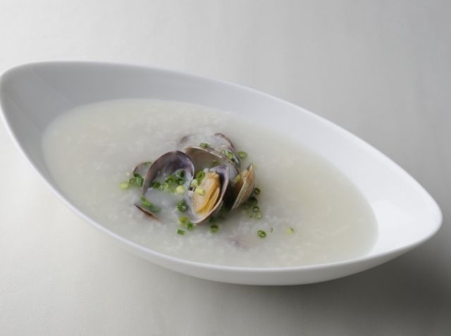 あさりの中華粥 - 田村 亮介シェフのレシピ。中国粥は、米粒とスープが一体化しているのが特徴です。とろみをつけるのに必要な米のでんぷん質が、洗米でなくならないように気をつけます。最低3時間は浸水させ、油をまぶして砕けやすくし、1時間かけて炊く。米粒が花開いたら食べごろのサインです。好みのアレンジで楽しんでください。
