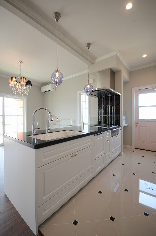 白 黒を基調としたシステムキッチンにピンクの勝手口で可愛い空間に