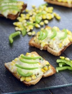 You will love the Cheesy Corn and Onion Toast not just for its cheesy flavour but also the interesting blend of textures. Sautéed onions, green chillies and corn are held together by a white sauce like paste, which makes it easy to apply the topping on the toast and also imparts a rich flavour. Grated cheese adds to the richness of this toast, but the smart move here is the use of raw capsicum strips, which imparts a wonderful crispness and a sharp taste to the whole arrangement.