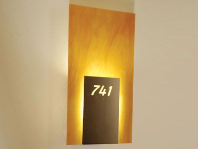 This attractive sconce provides room number identification as well as warm illumination to hallways in an upscale Paris hotel. The design hides the hardware and the beautiful resin diffuser radiates elegance. For more information, visit www.prgrha.com. © Product Resource Group, LLC