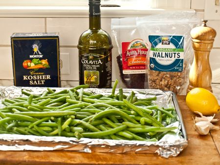 Roasted-Green-Beans-with-Cranberries-and-Walnuts  Toss a 2-pound bag of pre-trimmed and washed green beans with olive oil, salt, pepper, sugar and slivers of garlic. Roast in a high heat oven for about 25 minutes until tender, browned in spots and just starting to shrivel. Add lemon zest, lemon juice, dried cranberries and walnuts and serve.
