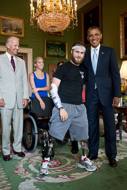 Vice President Joe Biden watches as President Barack Obama is photographed with Petty Officer Taylor Morris in the Green Room of the White House, July 26, 2012. The President presented a Purple Heart to Morris, who was participating in a tour of the White House with other wounded warriors and their families. (Official White House Photo by Pete Souza)