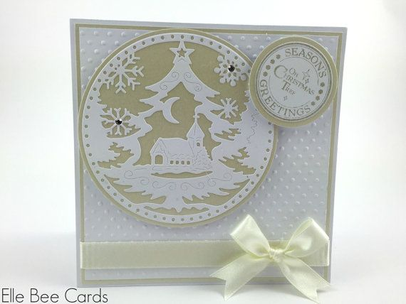 "A further card in my 2014 Handmade Christmas Card range and uses a beautiful pale gold and white colour scheme.  The card is 5.5"" x 5.5"" square and hinges at the top of the card. It is built with multiple layers, with a pretty white spotty embossed panel as the main background.  Mounted on this handmade Christmas card is a beautiful die-cut Tattered Lace snowglobe motif featuring a Christmas tree, church, moon and snowflakes."