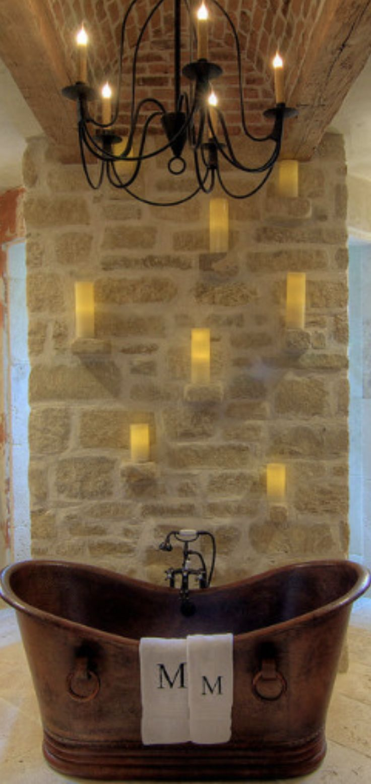 copper tub stone wall with candle shelves iron chandelier
