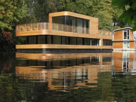 Technically a house barge, since it can't propel itself from one location to another, this home on the Eilbekkanal in Hamburg, Germany is warm, homey and modern with its curved wood exterior