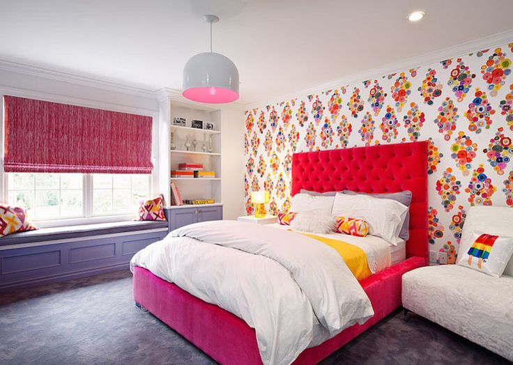 Fun girl's bedroom with pink and gray enamel pendant over multi-colored modern floral wallpaper highlighting the headboard wall with red velvet tufted bed layered with gray, white and yellow bed linens accented with a pair of red and yellow bolster pillows.