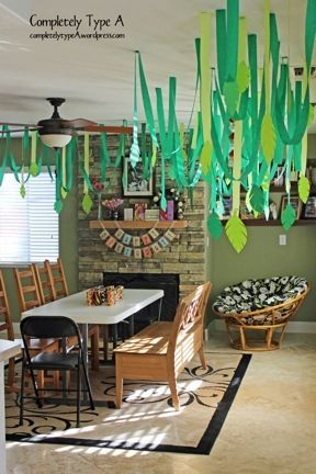 Jungle themed party: streamers, leaves, brown twisted butcher paper for branches, waterfall, bright rainbow flowers and parrots.