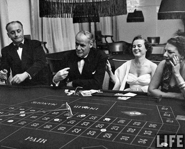 El asesor civil de la Fuerza Aérea de los Estados Unidos, C.E. Hall, y su esposa jugando a la ruleta junto a una amiga francesa, la señora Simon Loriot, en un casino de Marrakech, Marruecos, en 1952.