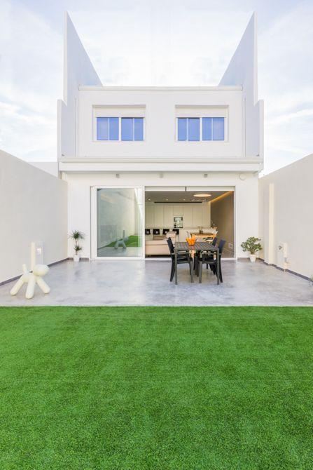 Jardín urbano con césped y terraza de hormigón en vivienda estilo nórdico - Chiralt Arquitectos Valencia