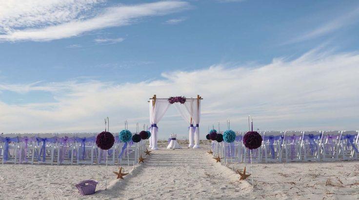 Pomanders line the beach wedding aisle