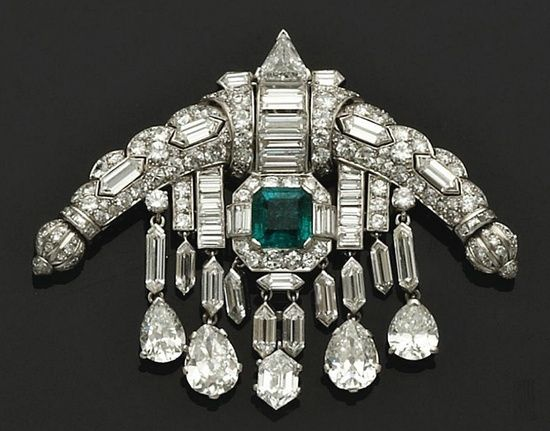 "The Queen`s Diamond & Emerald ""Sarpech"" brooch. A sarpech is really a turban ornament, worn by Hindu or Muslim Princes. this one was made in 1920 to an Art-Deco design, it features multiple cuts of diamonds in platinum & white gold. In the centre is a square emerald framed in diamonds & sitting between diamond tassels with pear-shaped diamond pendants."