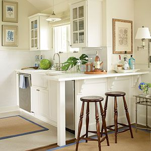 Designer Tricks for Small Spaces | Even small kitchens can Functional with Flair | make use of natural window lighting by accentuating with milky white palette,wall sconces, and pendant lighting to open up space to feel larger. CoastalLiving.com