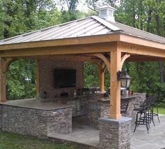 Cocina exterior entechada con asador, barra y bancos.