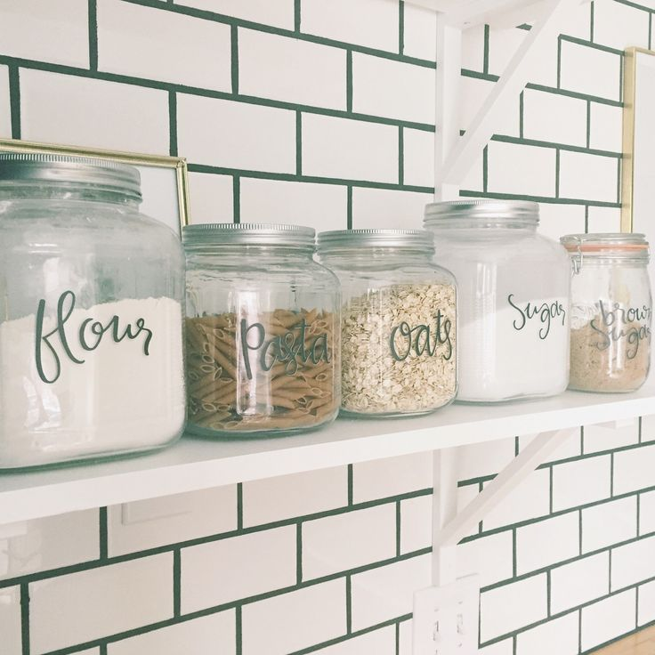 kitchen canisters labels in my kitchen on my open shelving in front of white subway tile with black grout
