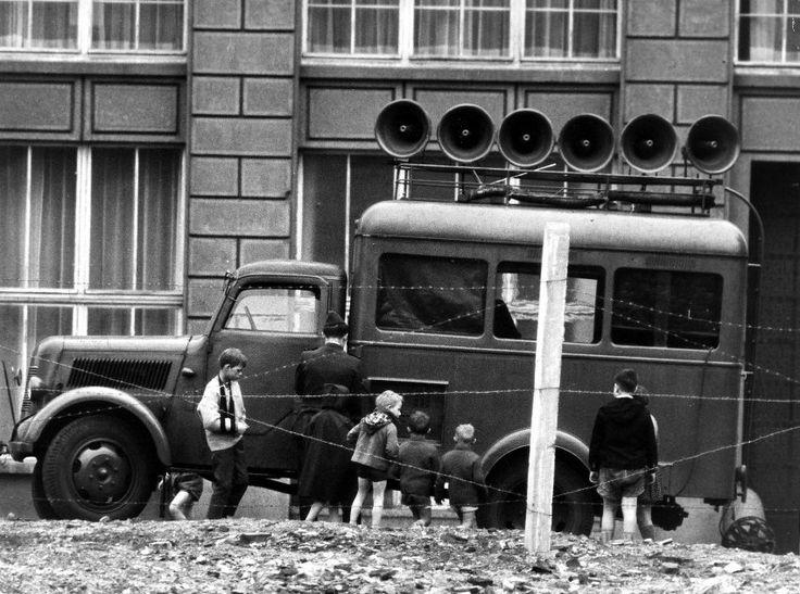 """Aufsehenerregend: Neugierige Kinder im Mai 1962 an einem der """"Roten Hugos"""" der DDR-Propagandaeinheiten. Das Ost-Pendant zum """"Studio am Stacheldraht"""" nannte sich """"Studio 13. August"""" - nach dem Tag, an dem der Mauerbau 1961 begonnen hatte. Gesendet wurden Propagandawortbeiträge und häufig auch satirisch umgetextete Schlager, in denen westliche Politiker angegriffen wurden. (Foto: ullstein bild - Dieter Otto)"""