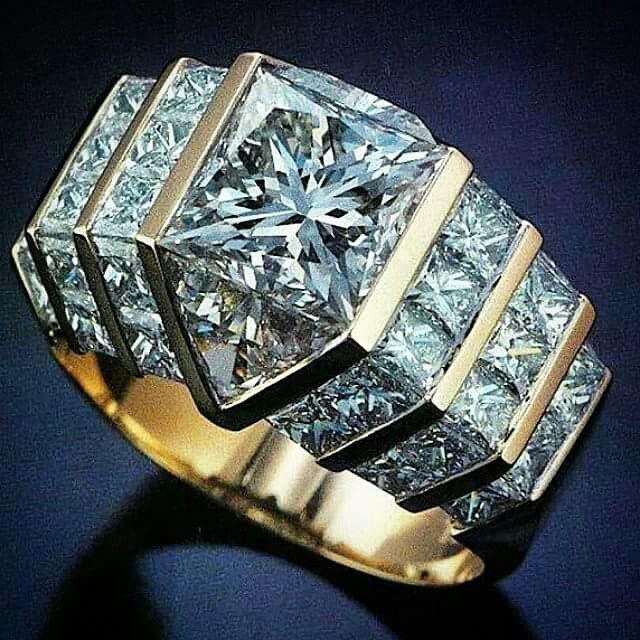 Prsten * velký diamant, vsazený do bílého zlata a zdobený malými diamanty.