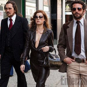 American Hustle Photo Featuring Christian Bale and Amy Adams -- Bradley Cooper co-stars in director David O. Russell's drama about a con man who gets roped into working alongside an FBI agent. -- http://wtch.it/iWlQD