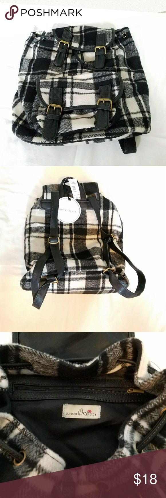 Back pack handbag Brand new Under One Sky back pack/handbag. Cotton shell and very durable..It has a flap and drawstring closure to keep your stuff secure, interior pocket, front pouch pockets, adjustable shoulder strap. This back pack features a chic plaid print.. new with tag.. Under One Sky Bags Backpacks
