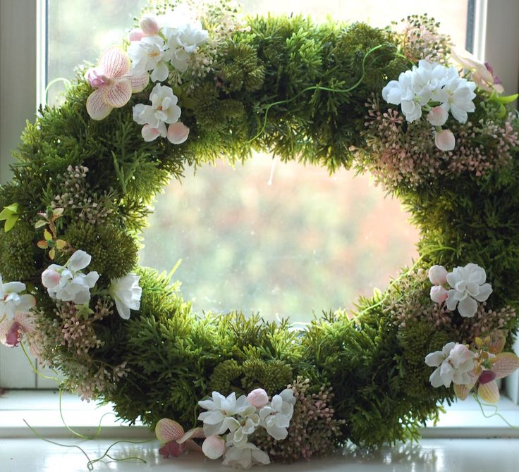 Lush green cypress wreath with wild lilac, apple blossoms, sedum twigs and moth orchids. One of a kind.