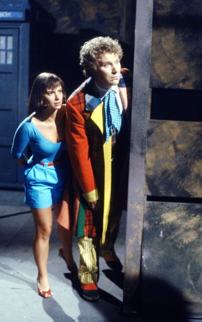 Colin Baker and Nicola Bryant sneaking around a corner