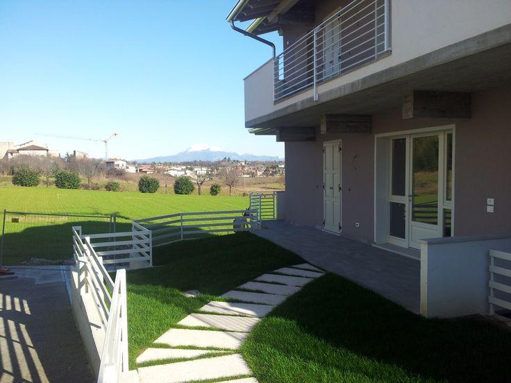 Il sole riscalda i colori dell'elegante giardino privato e sullo sfondo .... le colline ed il Baldo.