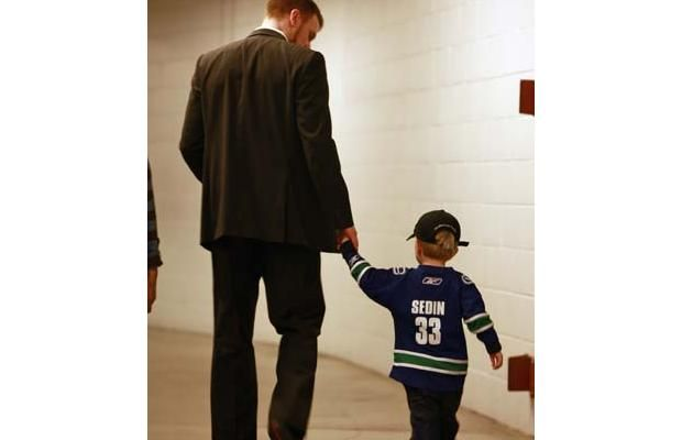 Henrik Sedin #33 of the Vancouver Canucks leaves the rink with his son Valter Sedin after a game. (Getty Images)