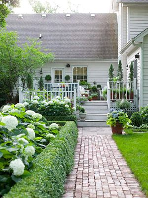 Boxwoods, bricks, and hydrangeas ~ perfect!  This could be a front porch or a back porch... but the curb appeal is strong for either case. Fabulous welcoming stone pathway with gorgeous evergreen hedges and beautiful ever blooming hydrangeas behind the hedges (called 'layering') and of course steps up to a gorgeous deck or porch. Love this look.