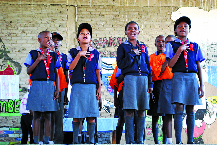 At the Okakarara Secondary School in South Africa, children perform in a World AIDS Day commemoration event. Improving education and livelihoods through the use of HIV vocabulary in language classes and presentations on HIV prevention are essential tools used by Peace Corps Volunteers to work toward an AIDS-free generation.