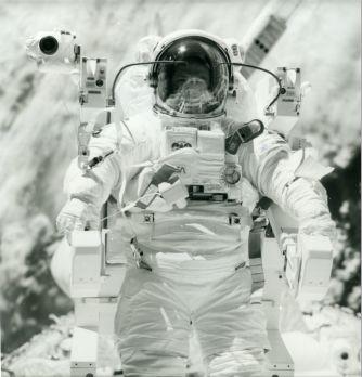 NASA 1984 Navette spatiale Challenger. L'astronaute Robert L. Stewart apparaît quelques mètres au-dessus de la soute de la navette spatiale réalisant avec Bruce McCandless les premiers tests de vol autonome sans lien dans l'espace. Tirage chromogénique d'époque sur papier Kodak. Numéro S84-27034 dans la marge. Logo Nasa et références. 20,3 x 25,4 cm avec marges.