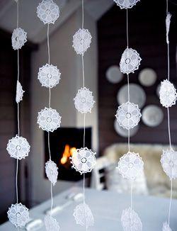 ijsbloemengordijn Knip bloemen uit een plastic kanten tafelkleed. Rijg wit touw 4x door het bloemetje, zodat het goed vast zit op 15 cm van elkaar. Maak de bloemenlinten vast aan een houten lat met de breedte van het raam 10 cm van elkaar.