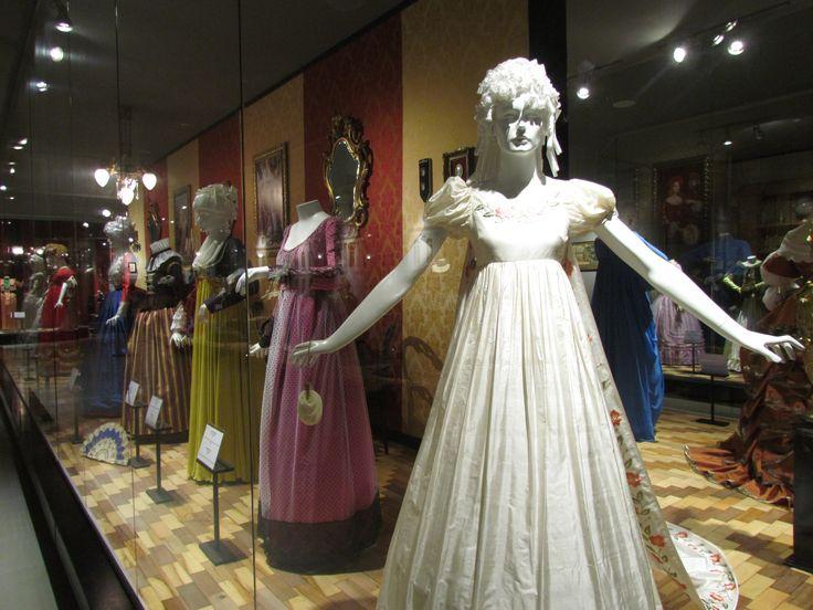 Moda Era Napoleônica. Vestidos longos, luvas, bolsas, véus de renda, flores artificiais para ornamentar cabelos e saias.