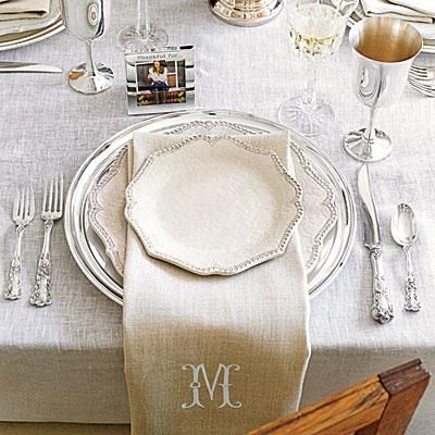 Fresh and Modern Thanksgiving Table | Keep your table simple and timeless by topping silver chargers with white plates. Layer an oversize linen napkin between the plates to add natural texture. | SouthernLiving.com
