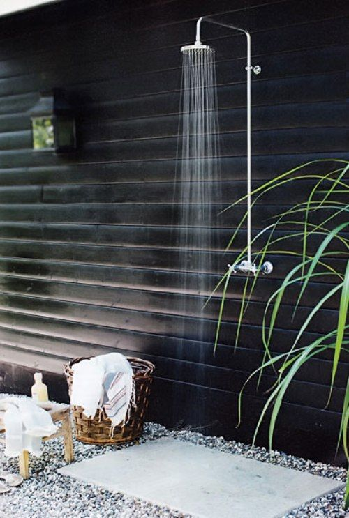 outdoor shower outside blue bathroom with 3 sided trellis