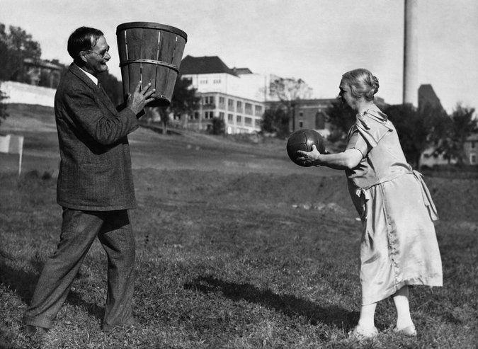 Le Docteur James Naismith, qui a inventé le basket ball en 1891 tient un panier pour jouer au sport avec sa femme, Maude, en 1928.