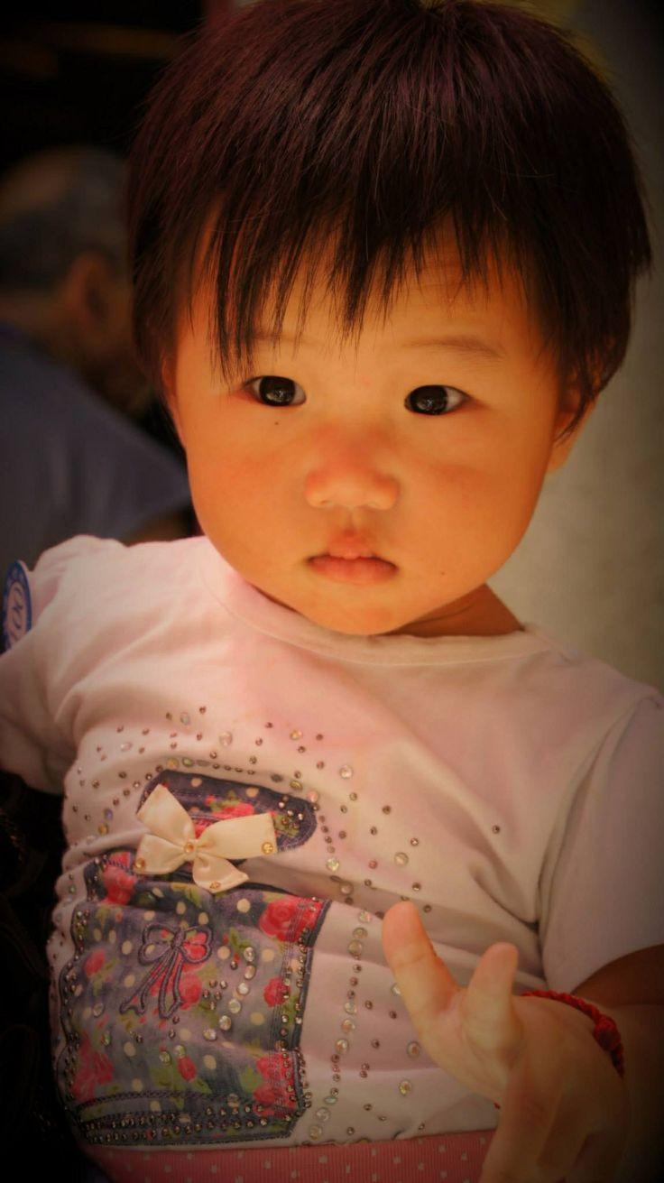 Une petite fille dans les bras de sa mère dans un temple de Macau, en Chine
