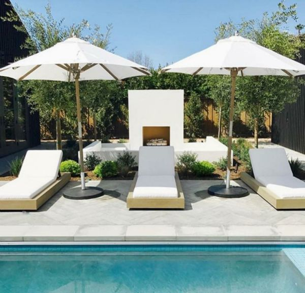 all white lounge chairs umbrellas and even an outdoor fireplace are once again an white elegant look and offer you that resort