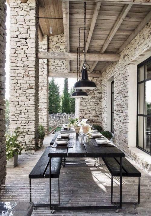 Überdachte Terrasse mit großem Tisch und Bänken aus schwarzem Holz   – Sophie François-Mülhens