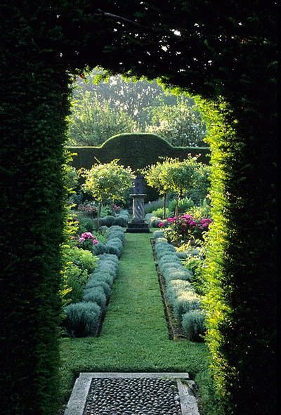 Cranbourne Manor gardens. Dorset. arch entrance in yew hedge to herb garden with grass path