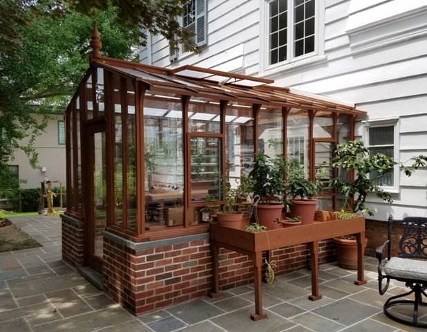 9x12 Garden Deluxe Greenhouse On A Brick Base Wall. Part Of A Nice Patio  Setting